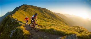 Two mountain bikers on a narrow path in the mountains