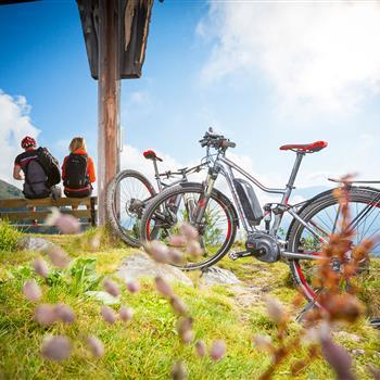 Zwei E-Bike Fahrer auf einer Bank am Gipfel