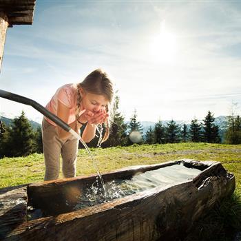 Mädchen trinkt aus einem Brunnen auf der Alm