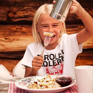 Girl sprinkling icing sugar over a Kaiserschmarrn