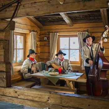Three musicians singing in a hut