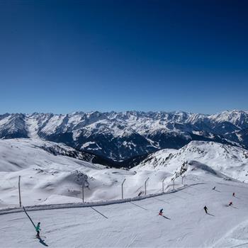 Panoramaansicht auf die Skipiste und die Bergipfel bei Sonnenschein