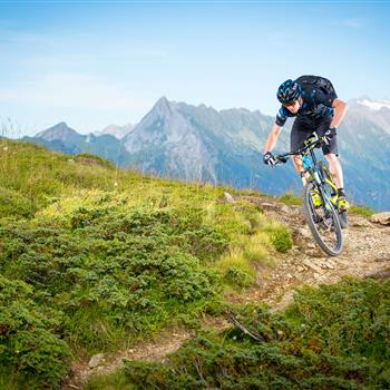 Mountain biker on a single trail in the mountains