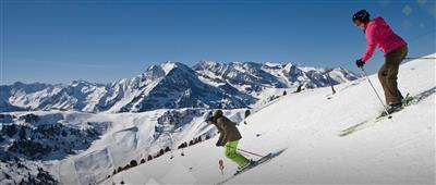 Zwei Skifahrer bei der Abfahrt auf der Piste