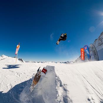 Snowboarder springt über Schanze