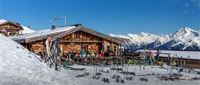 Exterior view of an alpine hut with skiers