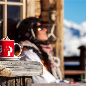Woman relaxes with coffee on the alpine terrace