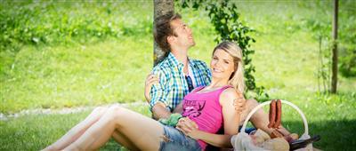 Pärchen mit Picknickkorb im Grünen