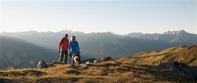 Couple hiking with dog in the mountains