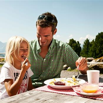 Father and daughter with Kaiserschmarrn on the alp