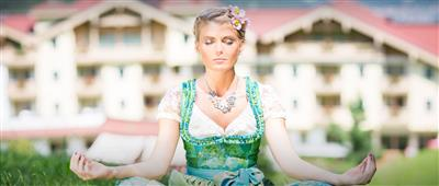 Woman in dirndls relaxes in a tailor-fashion sit