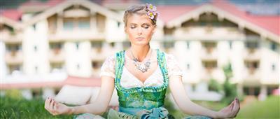 Frau im Dirndl meditiert im Schneidersitz
